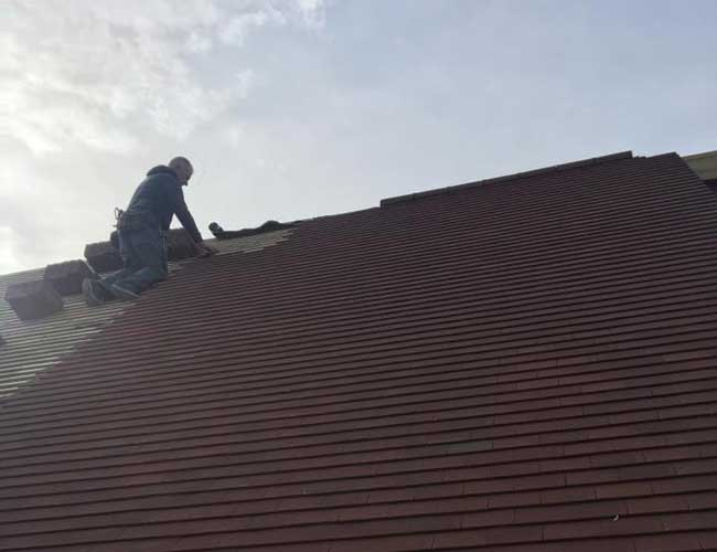 Man laying tiles on a roof in Kent
